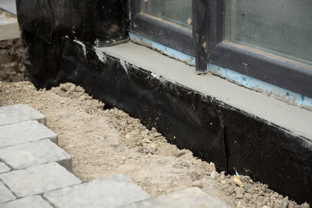 Waterproofing house foundation with spray on tar and roll waterproofing