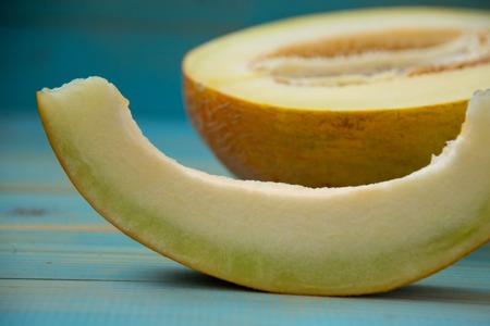 half ripe melon on a rustic, blue wooden background 版權商用圖片