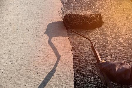 Roofer worker painting black coal tar or bitumen at concrete