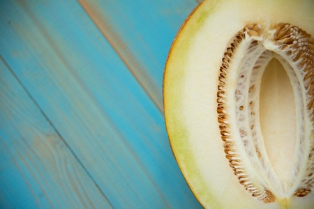 half ripe melon on a rustic, blue wooden background 版權商用圖片