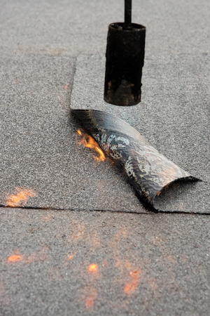 Preheating the edges of the roofing material.