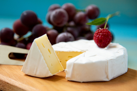 cheese camembert with raspberries and grapes on table Reklamní fotografie - 112806851