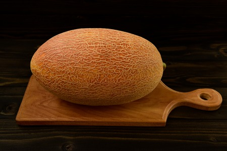 Fresh melon on old black wooden table