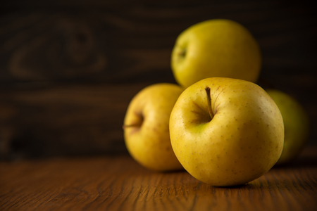 Yellow apples, on the dark wooden background. Copy space.