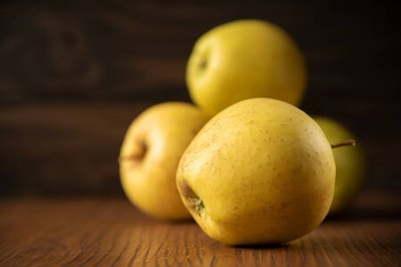 Yellow apple on the wooden vintage background