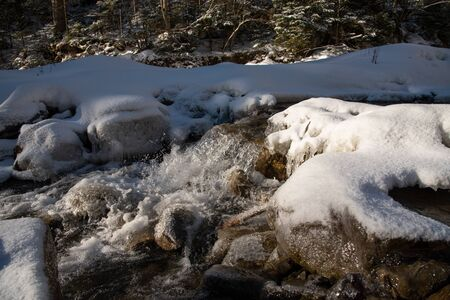 Water flowing in rapids over stone, in the winter mountains 版權商用圖片