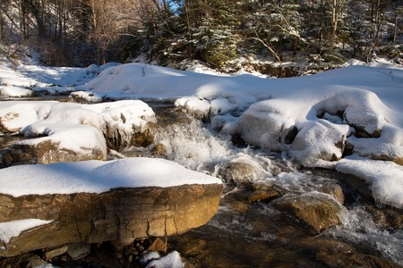Water flowing in rapids over stone, in the winter mountains 写真素材