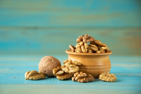 Walnuts on blue rustic table in wooden bowl 写真素材 - 121838851
