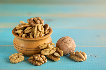 Walnuts on blue rustic table in wooden bowl