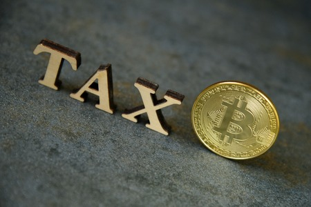 Bitcoin and wooden letters TAX on stone background