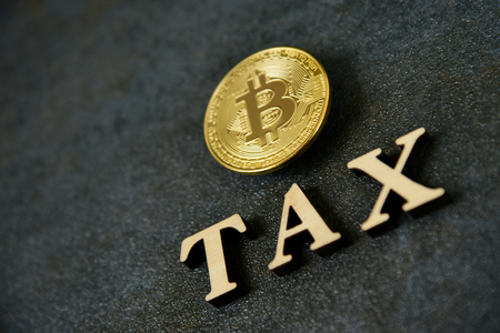 Bitcoin and wooden letters TAX on stone background 写真素材 - 121820614