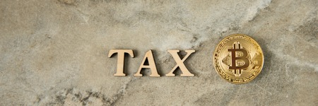 Bitcoin and wooden letters TAX on stone background 写真素材 - 122659639