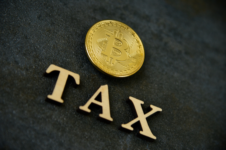 Bitcoin and wooden letters TAX on stone background 写真素材 - 122659640