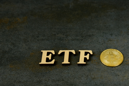 Bitcoin coin with ETF text on stone background