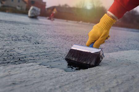 Le travailleur applique le mastic de bitume sur la base