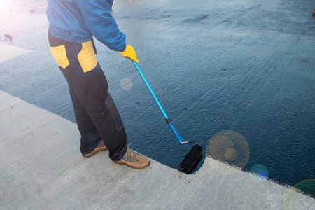 Worker applies bitumen mastic on the foundation Foto de archivo