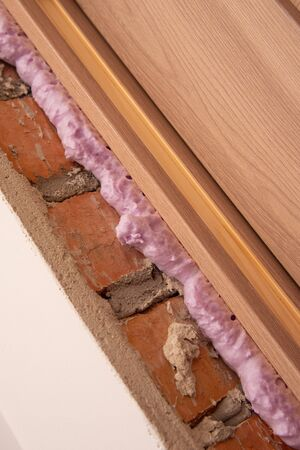 Mounting foam. Installation of doors using polyurethane foam mounting.  Gap between the window and the wall with insulation  foam to insulate. DIY concept