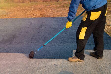 Revêtement imperméabilisant. Le travailleur applique du mastic de bitume sur la fondation. Le couvreur recouvre l'apprêt imperméabilisant au bitume modifié polymère sur le toit, avec une brosse à rouleau. Banque d'images