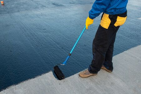 Trabajador aplica masilla bituminosa en la base Foto de archivo