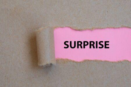 SURPRISE, word written under torn paper Image.