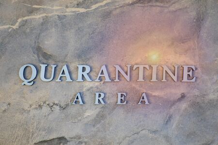 quarantine area , writen wooden letters on stone background 写真素材