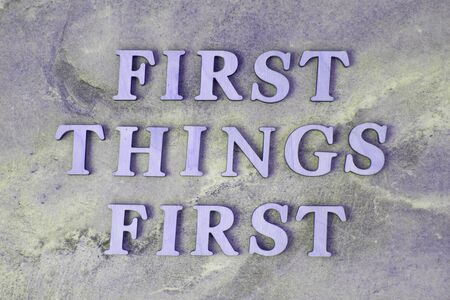 first things first , writen wooden letters on stone background