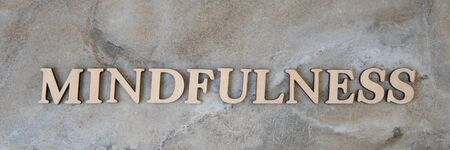 mindfulness , writen wooden letters on stone background