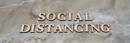 social distancing , writen wooden letters on stone background 写真素材