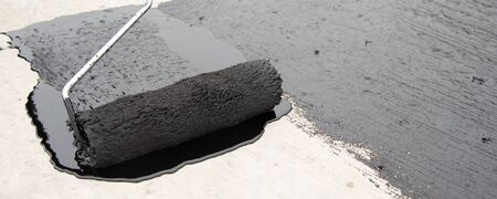 Worker applies bitumen mastic on the foundation Reklamní fotografie