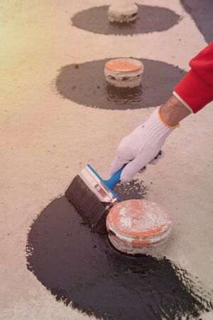 Worker applies bitumen mastic on the foundation