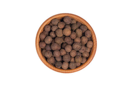 Allspice pepper, peppercorns in wooden bowl isolated