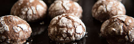 Cracked chocolate cookies with icing sugar on a pan Stock fotó