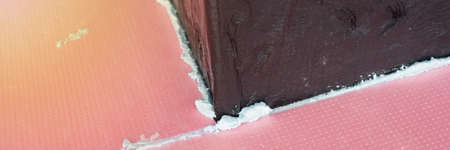 Construction foam between pink extruded plastic sheets
