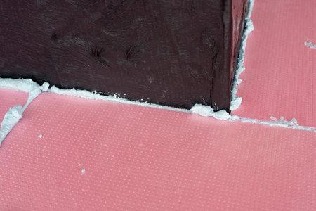 Construction foam between pink extruded styro foam sheets