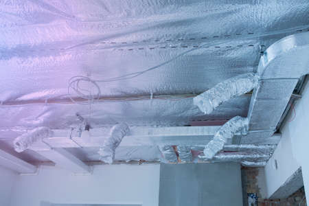 Ventilation pipes in silver insulation material on ceiling