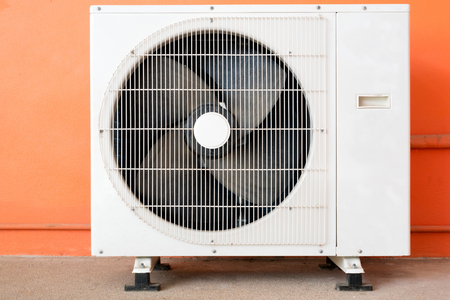 Condensing Unit of Air Conditioner at a Red-Orange Painted Wall Imagens