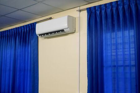 Air Conditioner between Window with Blue Curtains