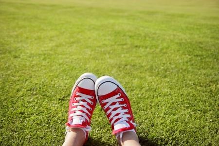 F��e in Turnschuhen im gr�nen Gras Lizenzfreie Bilder
