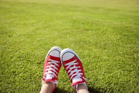 freedom park: Feet in sneakers in green grass Stock Photo