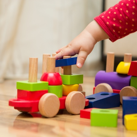 Baby hand playing with wooden toys Banco de Imagens