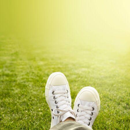 Ein Paar wei�e Turnschuhe im Gras in der Sonne