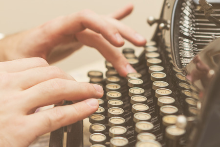 Hände schreiben auf alte Schreibmaschine