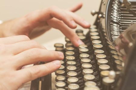 Handen schrijven op oude typemachine
