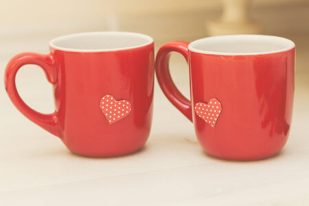 Photo of cute red cups with handmade paper heart Stock Photo