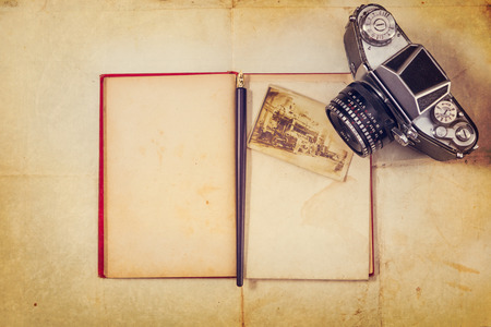 Background with vintage photo,empty open book and camera photo