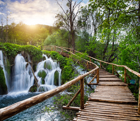 Beautiful view of waterfalls and pathway in the sunshine in Plitvice Lakes National Park. Banco de Imagens