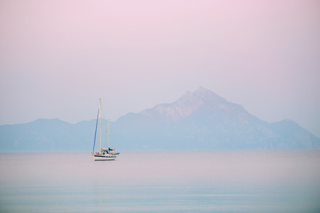 Sunrise with yacht and blue water ocean with Athos mountain in the background - Greece, Europe