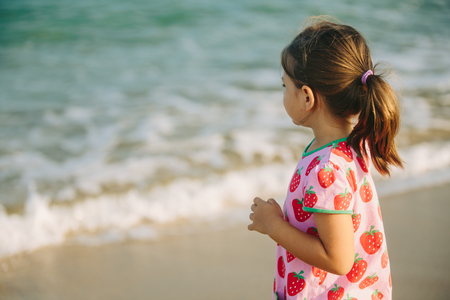 jolie fille: Petite fille sur la plage à la recherche de l'inconnu