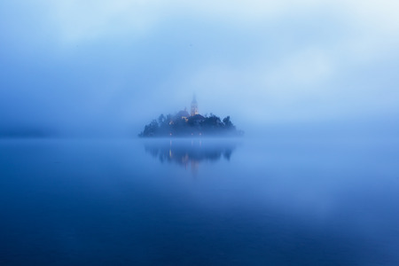 dreamscape: Panorama view of the famous island with old church in the city of Bled Blejsko jezero. Dreamy scene with mist and cold colors. Slovenia, Europe