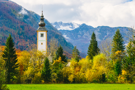 Gorgeous view of colorful autumnal scene of famous Church of St John the Baptist at Bohinj Lake. In the background the Vogel mountain. Ribicev Laz, touristic village in Slovenia